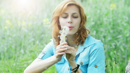 girl blowing on a bouquet of dandelions, slow motion