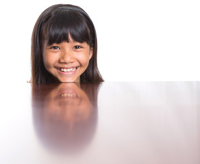 Young Asian Malay girl with face reflection on a table surface