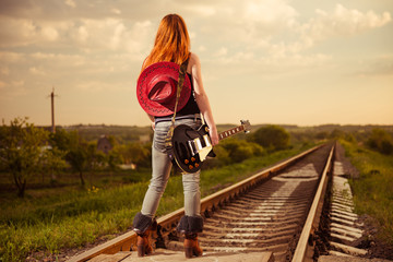 woman with guitar at railway trucks