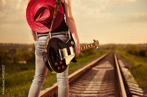 woman with guitar at railway road