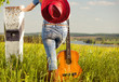 woman in jeans at spring meadow with guitar