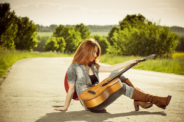 woman with guitar at freeway turn