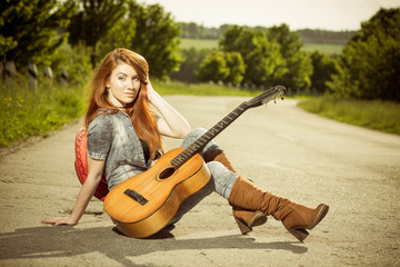 woman with guitar at asphalt road