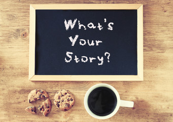 blackboard with the phrase whats your storry and cup of coffee a