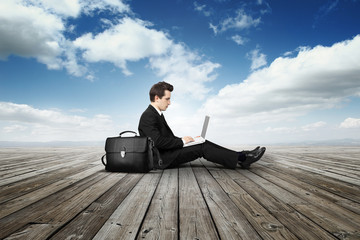 business man with laptop on wooden floor