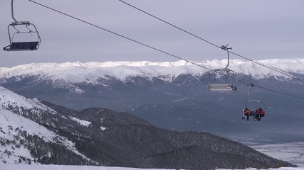 Skiers and snowboarders on a chairlift of ski resort Bansko