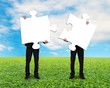 Two men holding blank puzzles on grass ground