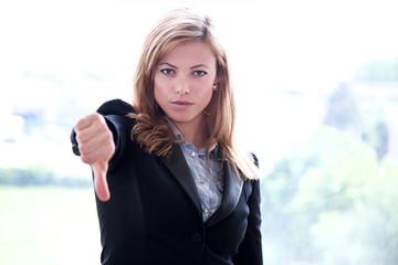 Junge blonde Frau zeigt Daumen runter und schmollt