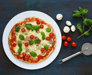 Pizza with mushrooms, tomatoes and basil