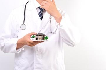 住宅の模型を持っている白衣の医者