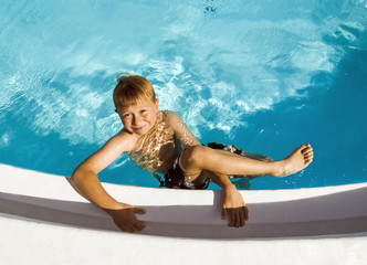 cute boy in swimming pool laughes and poses