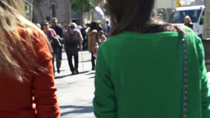 Women turning to the camera on the street, slow motion shot at 1