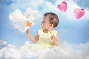 Kind mit Windrad auf einer Wolke