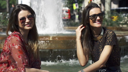Women smiling to the camera on the fountain, slow motion shot at