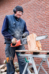 Man working with chain saw on trunk