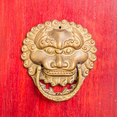 ancient red doors with gilded studs and lion head door knockers