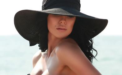 Portrait of beautiful brunette woman in black elegant hat
