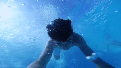 Happy active teenage in the swimming pool, underwater view