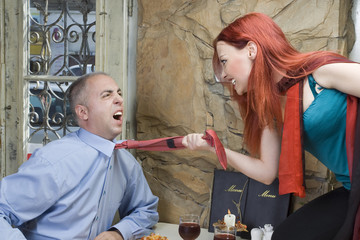 Furious and angry woman strangling him with a tie.