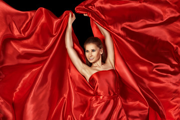 beautiful woman in red silk dress flying