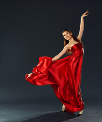 beautiful ballerina dancing a long red dress flying