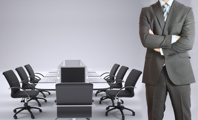 Businessman and conference table with laptops