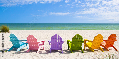 Fotobehang Strand Adirondack Beach Chairs on a Sun Beach in front of a Holiday Vac