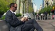 businessman using his cellphone and sitting on a bench in a city