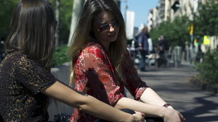Women sitting on street bench and chatting, steadycam shot