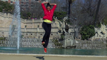 Happy woman jumping and rising hands, slow motion shot at 120fps