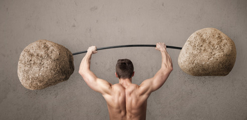 muscular man lifting large rock stone weights