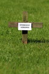 """Kreuz auf  Rasen mit Schild """"Sterbegeldvorsorge"""""""
