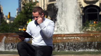 successful businessman looking at good results on tablet and sit