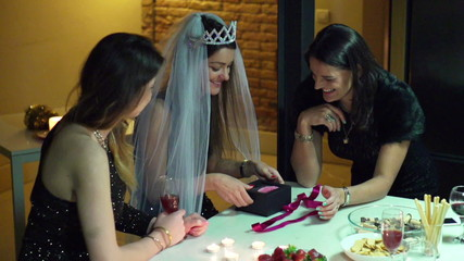young woman opening a gift at the bachelorette party, slow motio