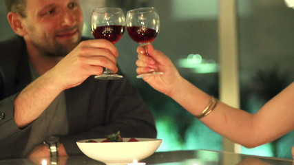 couple making a toast with glasses of wine during a romantic eve