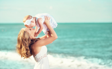 happy family in white dress. Mother throws up baby in the sky