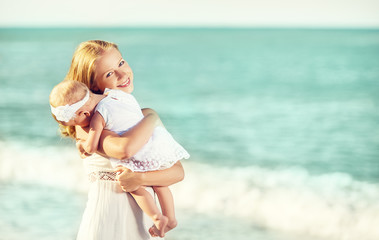 happy family in white dress. Mother hugs baby in the sky