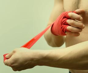 Боксер забинтовывает руки перед поединком