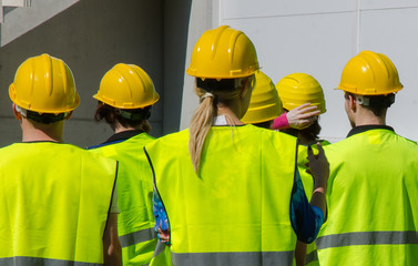 Group of workers in hardhats. View from the back.