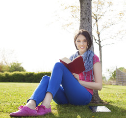 Happy young woman sitting on grass and reading a book.