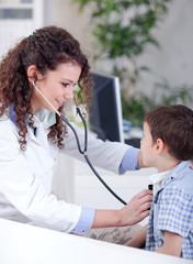 Young smiling friendly female doctor examining a little boy