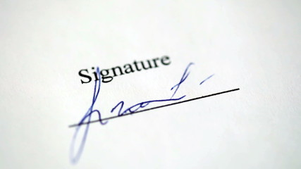 Close-up of a  hand writing a signature on the document