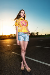 Beautiful young woman walking on asphalt road