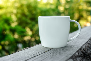 White coffee cup on wooden desk outdoors