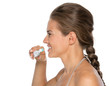 Profile portrait of young woman brushing teeth