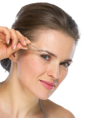 Young woman using tweezers on brow