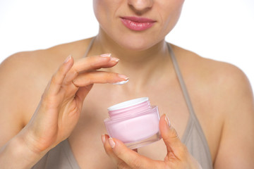 Closeup on young woman applying creme