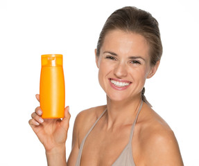 Portrait of happy young woman showing bottle of sun screen creme