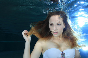 Young woman underwater making bubbles