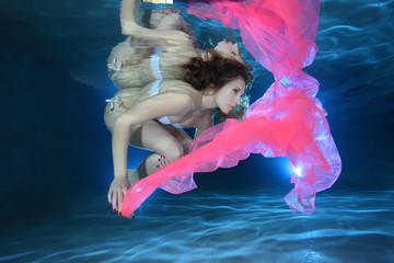 Young woman underwater with pink foulard